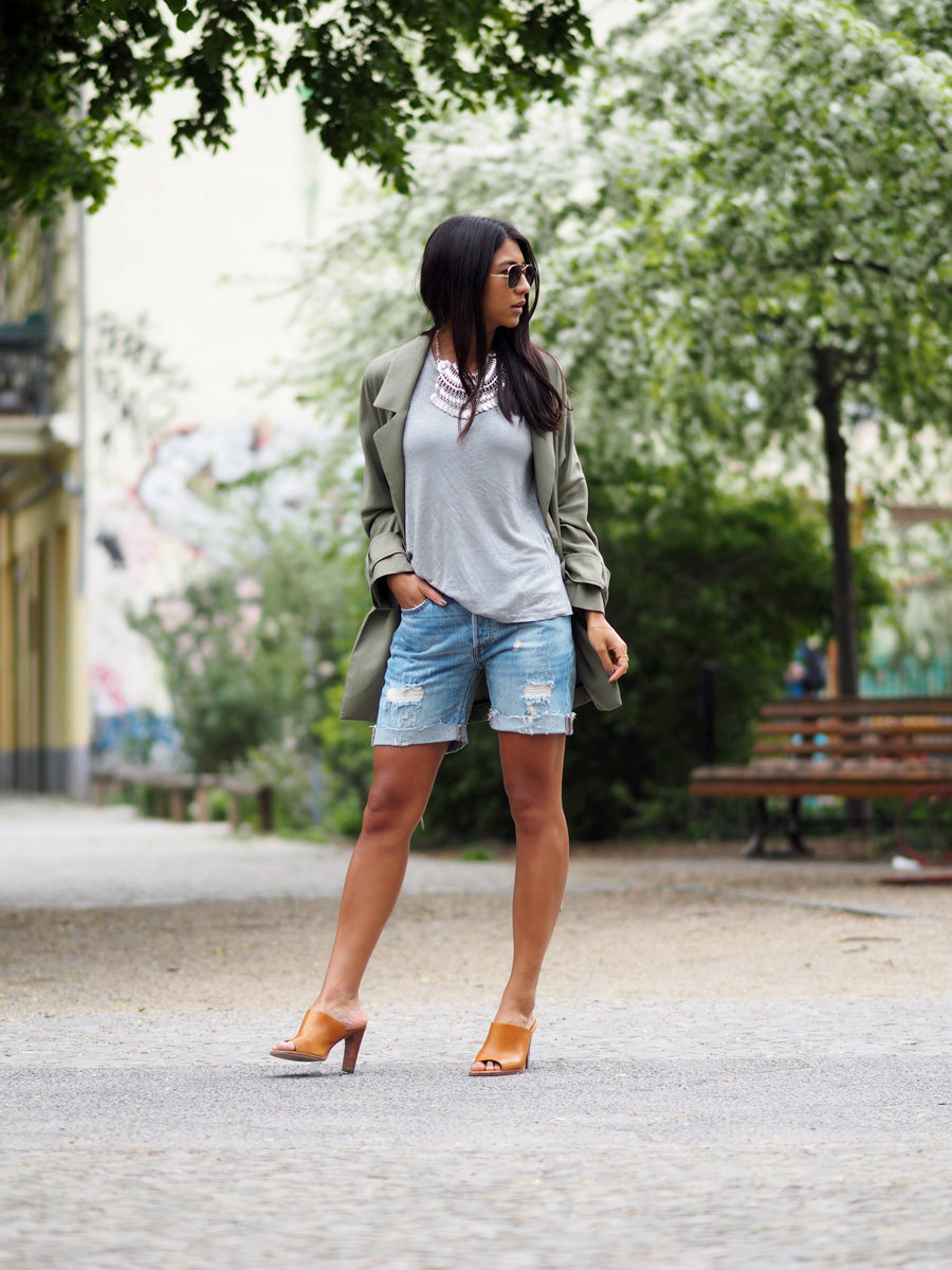 Kayla Seah is wearing a grey top from Edited, denim shorts from Levi's, orange mules from & Other Stories
