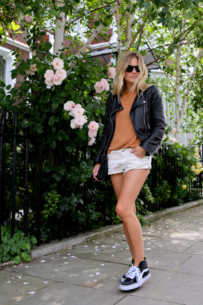 Basics: Shorts, leather jacket and high-tops to creating an easy Tomboy Style Outfit. Via Lucy Williams  T-shirt: Toteme, Shorts: Free People, Trainers: Vans, Leather Jacket: Belstaff