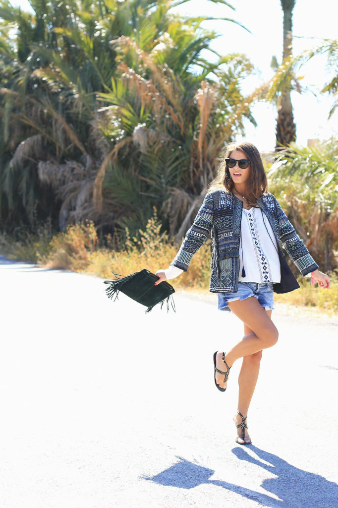 Bohemian Summer Outfits: Jessie Chanes is wearing a blue printed Zara jacket, a white Vila Clothes blouse, denim shorts from Zara, black studded Mas34 sandals and a fringed clutch bag from Asos