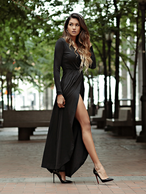 Dawilda Gonzalez is dressed in an elegant black maxi wrap dress with a high slit  Dress: Miguel Genao