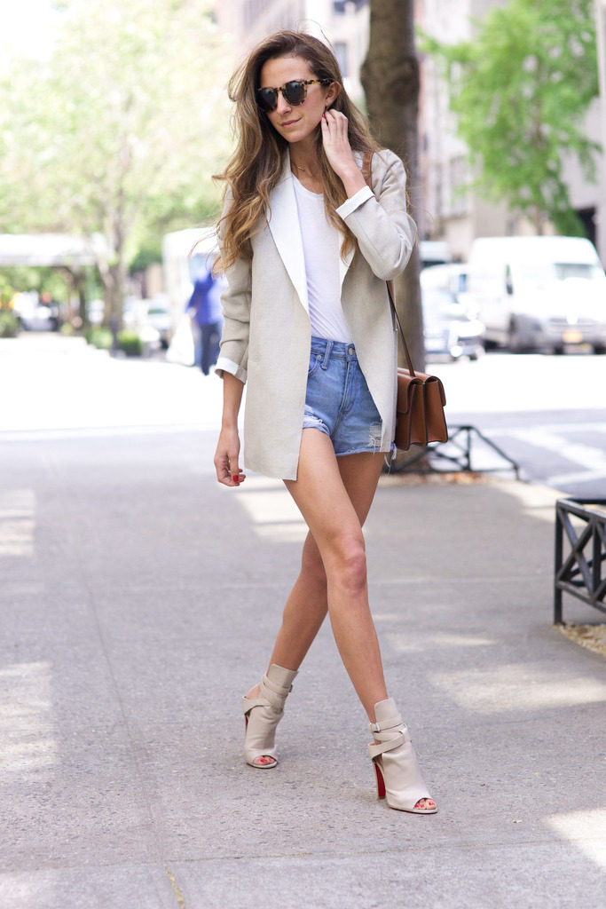 Arielle Nachami in a neutral beige blazer, denim cut off shorts, a white tee and heels   Blazer: Sandro, Shorts: Lovers & Friends, Shoes: Christian Louboutin