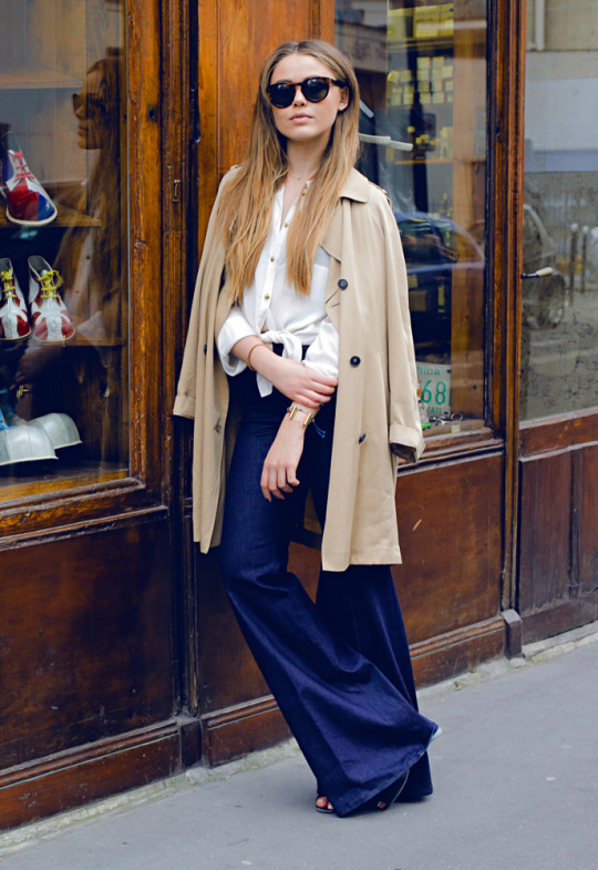 Kristina Bazan in a pair of dark denim flares, a white blouse and creme mac coat Jeans: 7 For All Mankind, Blouse: H&M, Coat: Topshop