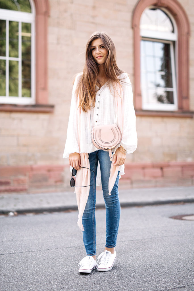 The main element of the perfect boho style is a casual tone, which Valerie Husemann shows perfectly. A white blouse, creme mini bag, plain sneakers and light wash denim jeans are an essential to achieve this look.  Blouse: Free People, Jeans: Noisy May, Sneakers: Converse, Bag: Chloe