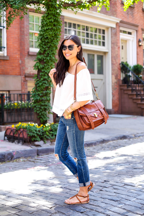 Via Just The Design: Kat Tanita is wearing an off the shoulder Otte blouse with a pair of Rag & Bone boyfriend jeans, Illesteva sunglasses, beige K. Jacques sandals and a Proenza Schouler bag