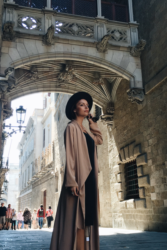 Just The Design: Mafalda Castro in a nude draped maxi coat, simple black dress and a sun hat to accessorise the outfit.