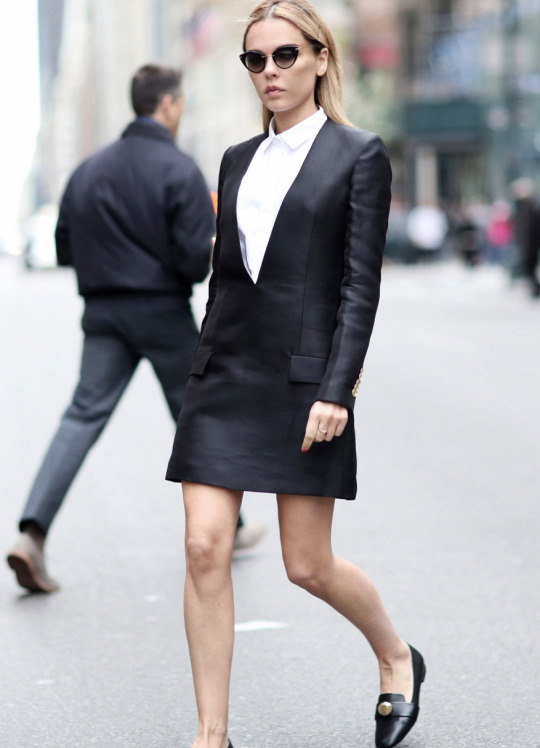 Street Style Fashion: Evangelie Smyrniotaki is wearing a plain white Saint Laurent shirt under a V neck black Acne leather dress with a pair of Christopher Kane pumps