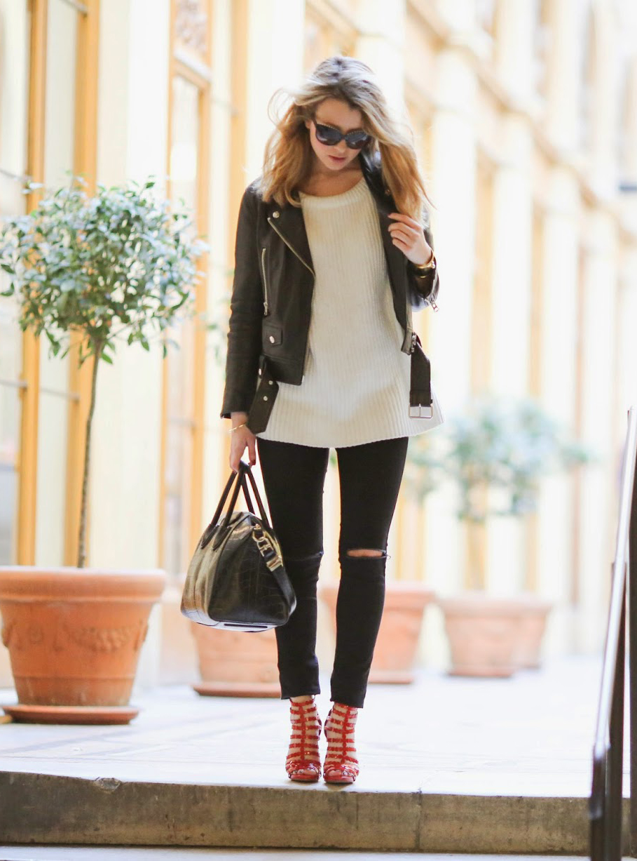 Caroline Louis is wearing an Acne black leather jacket, Oasis skinny jeans, red Alaia heels and a creme sweater