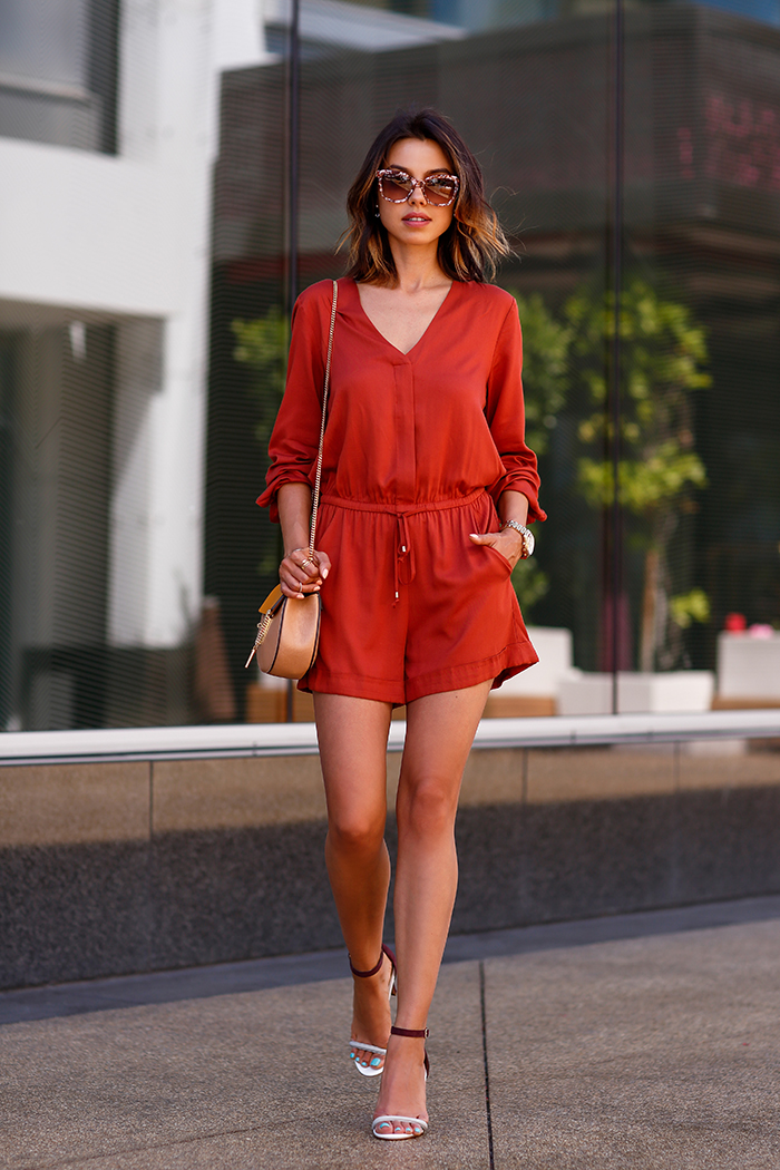 Annabelle Fleur in a blood orange jumpsuit, heeled sandals and a beige side bag Jumpsuit: H&M, Bag: Chloe