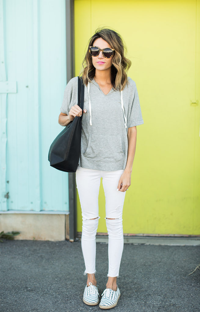 Christine Andrew is wearing an Old Navy grey sleeveless hoodie with a pair of white Nordstrom denim jeans and striped flat sneakers