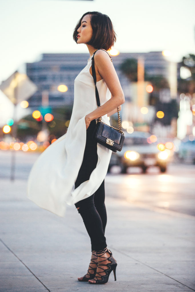 Chriselle Lim showing off the long over long trend, in a fringed white dress over black skinny jeans   Dress: Haney, Jeans: Hudson