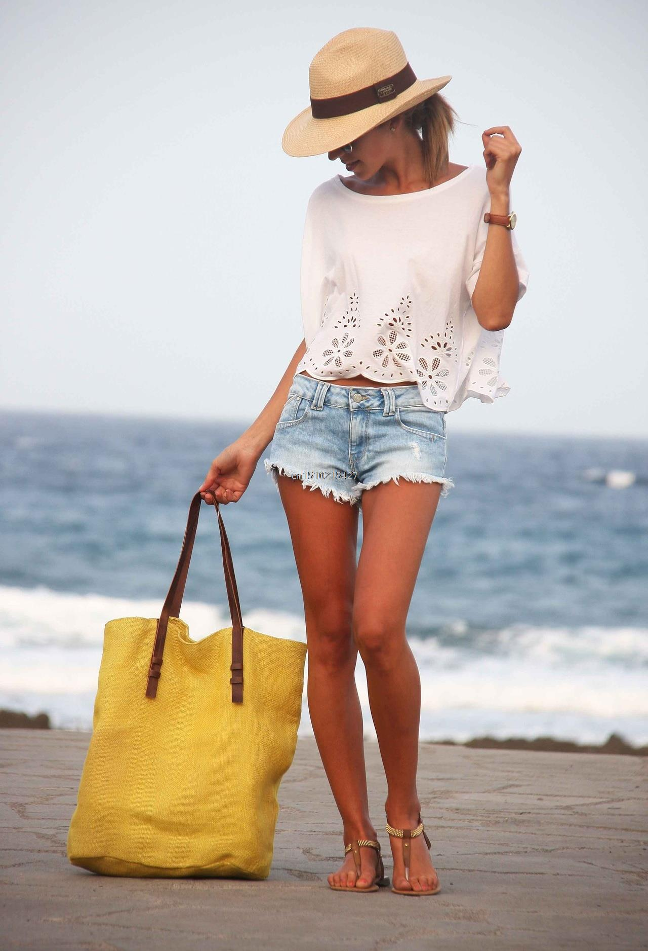 Frayed denim shorts and a simple white top is the ultimate beach look. Pair with a wide brimmed straw hat for added effect. Via Unknown Blogger. Brands not specified.