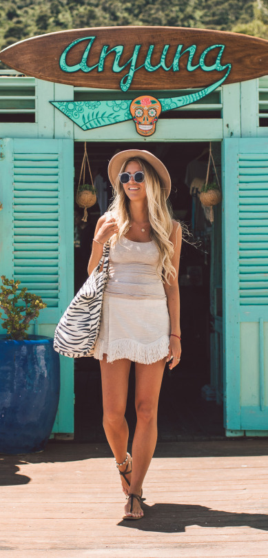 Janni Deler is wearing a cute tasselled mini skirt with a tank top as a sexy beach cover up which is perfect for strolling the promenade on hot afternoons. Wear this look with sandals and a straw hat to steal Janni's style! Top: H&M, Skirt: Storets, Bag: Ragdoll LA.