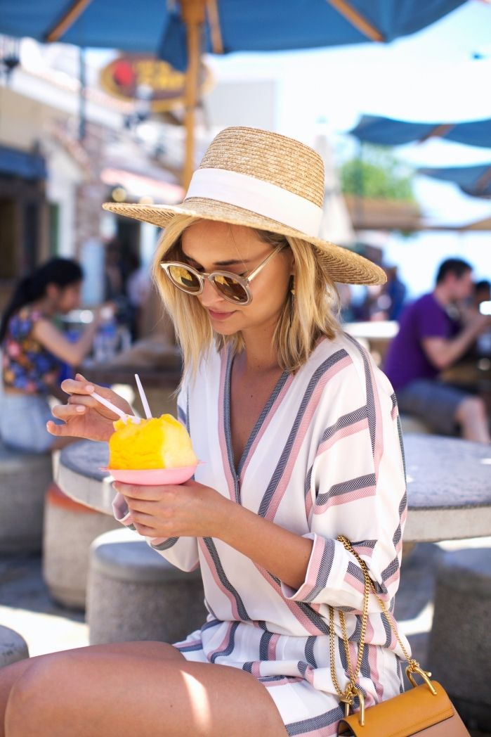 Outfits to wear to the beach: This pink, grey and and white striped jumpsuit is an ideal jumpsuit to wear on top for your swimwear when at the beach. Via Liz Cherkasova Jumpsuit: Maje, Hat: J.Crew, Bag: Chloe, Sunglasses: Karen Walker