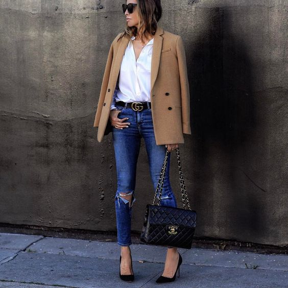 Sasha Simon wears a double breasted camel blazer with an open white button down and distressed denim skinny jeans to create this elegant work-ready style. Brands not specified.