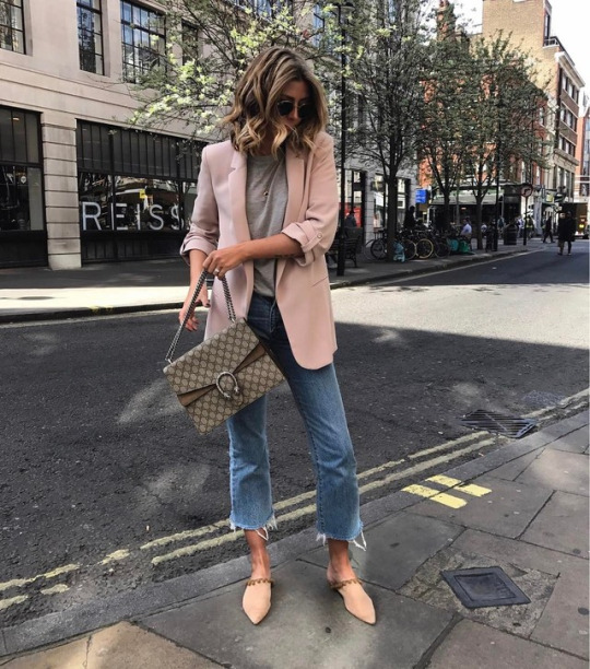 Emma Hill is wearing a blazer in a playful shade of pale pink, paired with roughly cut-off denim jeans, a grey tee, and pastel coloured flats.   Bag: Gucci, Shoes: Revolve, Blazer: Zara.