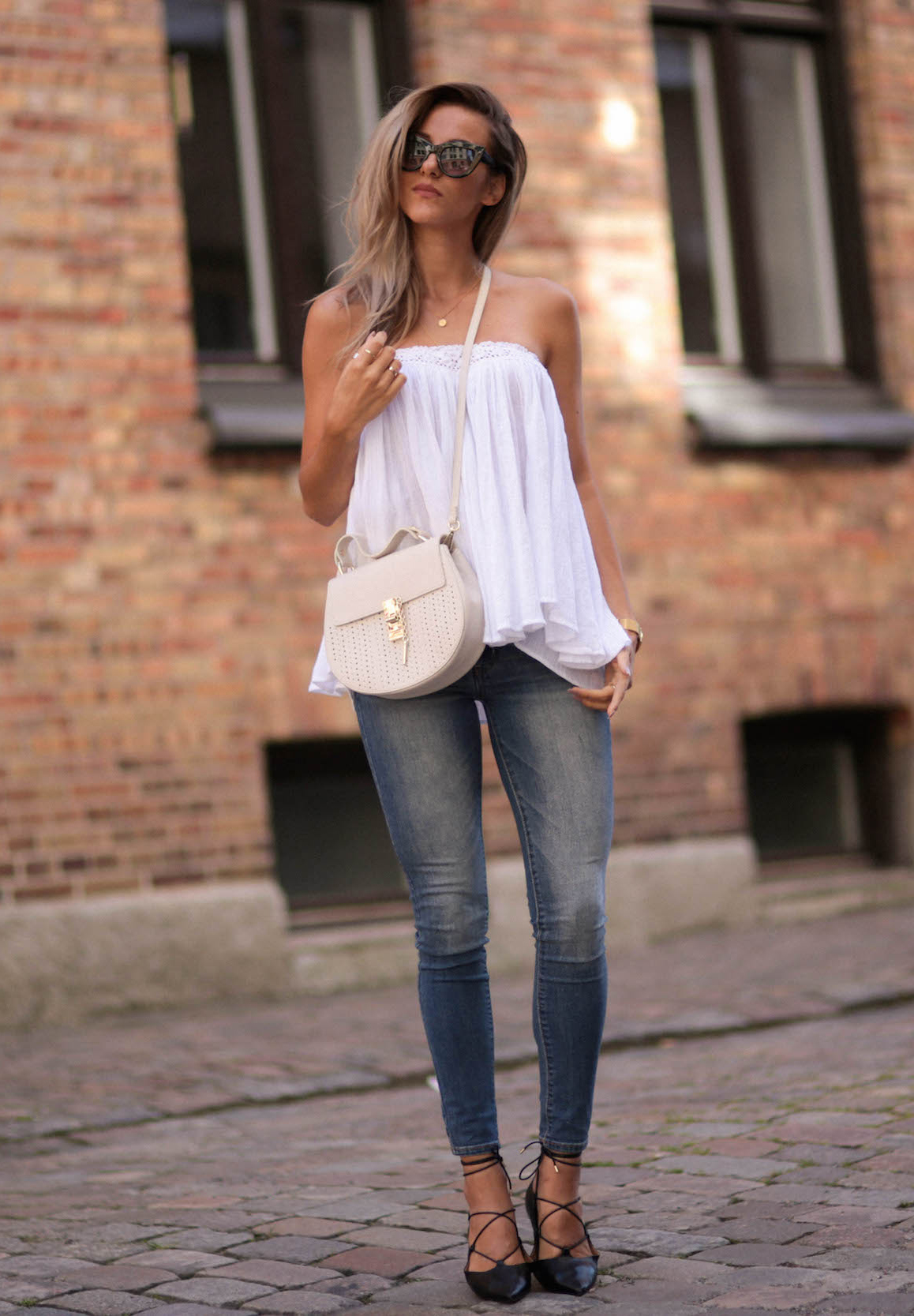 A simple white blouse and skinny denim jeans can make the perfect every day summer outfit. Sendi Skopljak wears this pretty and casual outfit with strappy sandals and stylish shades. Top: Make way, Bag: Chiquelle, Shoes: Topshop, Watch: Larsson & Jennings.