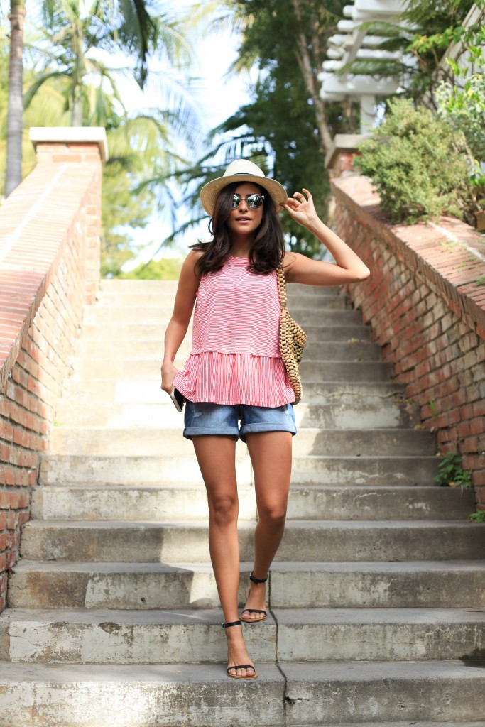 Sazan Barzani looks cute and feminine in this pink ruffle hem top, paired with classic denim shorts and open toe sandals. Finish the look with a straw hat and sunnies to get this summer feel! Outfit: Old Navy.