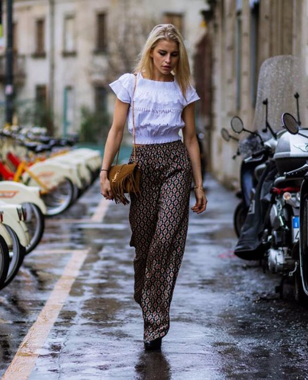 Caroline Daur wears a pair of floaty patterned palazzo trousers with an adorable cropped white blouse and a fringed leather bag. This look is hippy chic at its finest! Coat: Gestuz, Top: Pink, Trousers: Zara, Shoes: Topshop, Case :Saint Laurent.