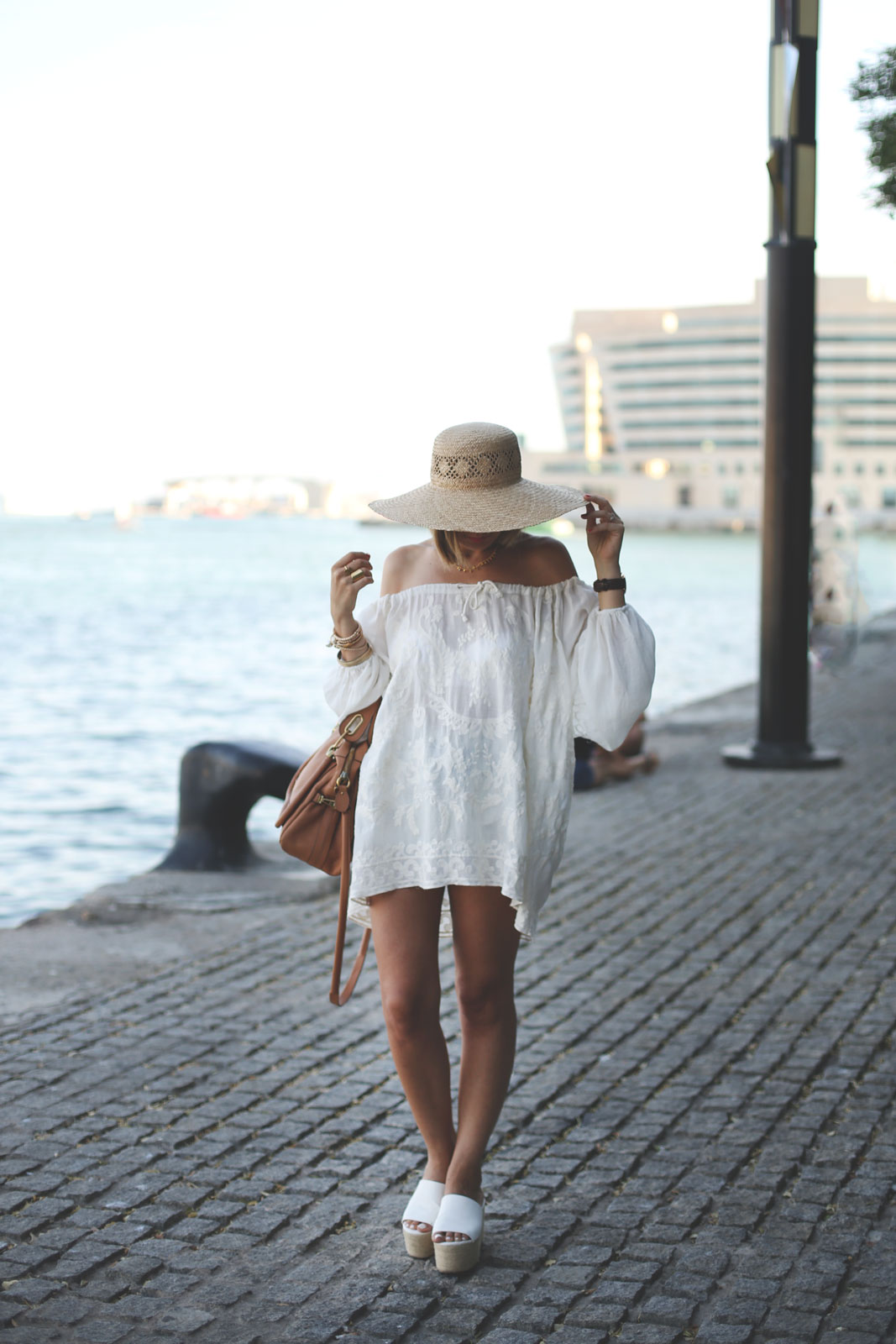 An all-white outfit with a white off-the-shoulder dress and platforms. Via Priscila Betancort Dress: Pau'la Boutique, Bag: Chloé