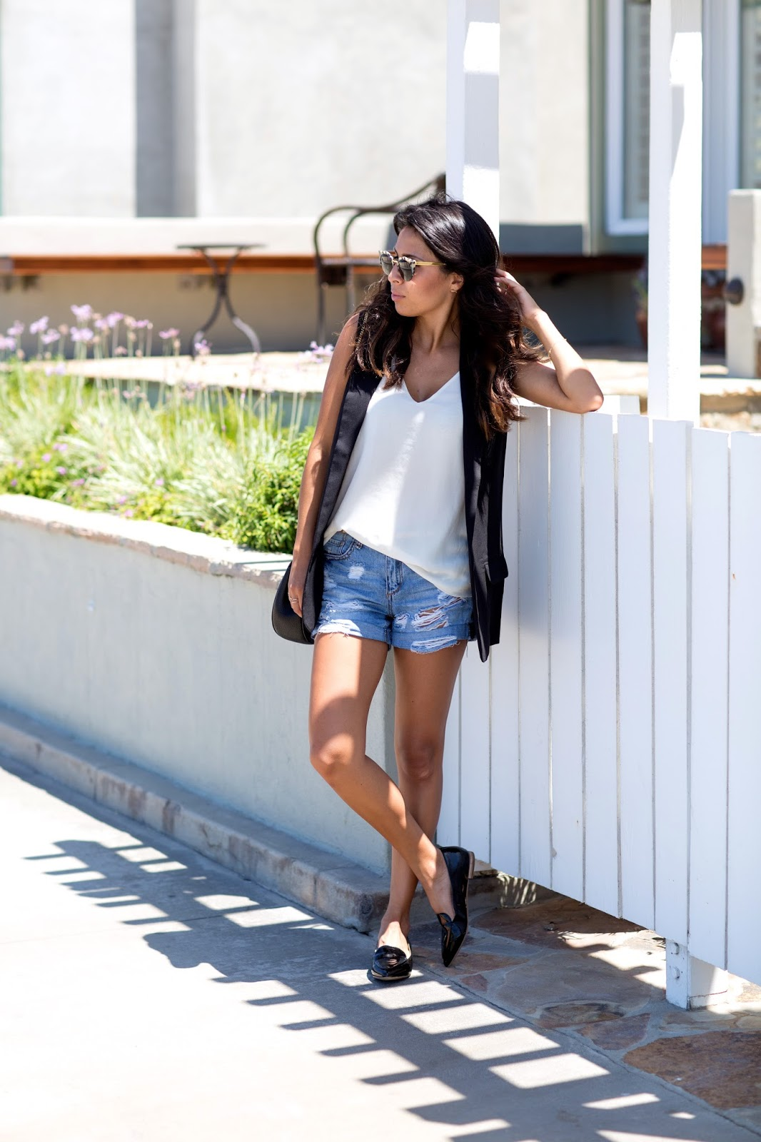 Ashley Torres is looking cool, calm, and ready for summer in this cute denim shorts outfit, paired with black penny loafers and a matching black vest. This look is simplistic but stylish, and you can never go wrong with it! Vest: BB Dakota, Shorts: Forever 21, Tank: Zara.
