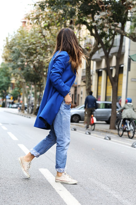 Aida Domenech wears a pair of white All Stars with rolled up denim jeans and a funky blue coat. Coat: Mango, Shirt: Urban Outfiters, Jeans: Re Done, Shoes: Converse.