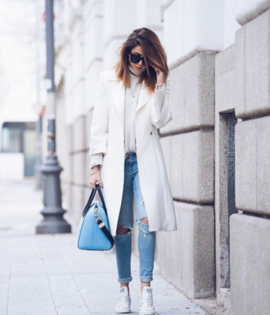 Wearing white converse with a matching white coat can create a gorgeous winter look. Nicoletta Reggio wears the trend with ripped denim jeans and a cute blue Givenchy bag. Coat: Castellani, Sweater & Jeans: Zara, Shoes: Converse from Sarenza.it, Bag: Givenchy, Sunglasses: Valleyeyewear.
