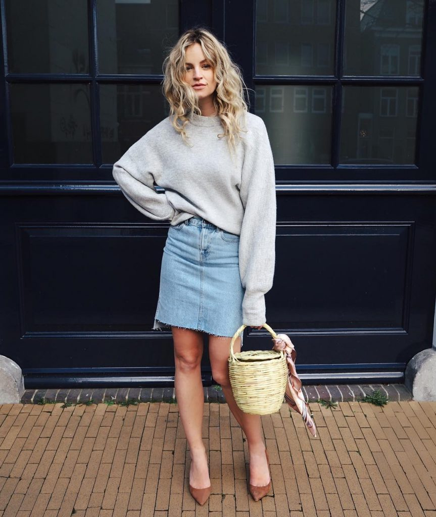 Anouk Yve wears a denim mini skirt with an oversized grey sweater, brown leather flats, and an adorable wicker basket. This look is ideal for those sunny spring days! Skirt: Dr Denim, Top: Weekday Stores, Basket: Etsy.