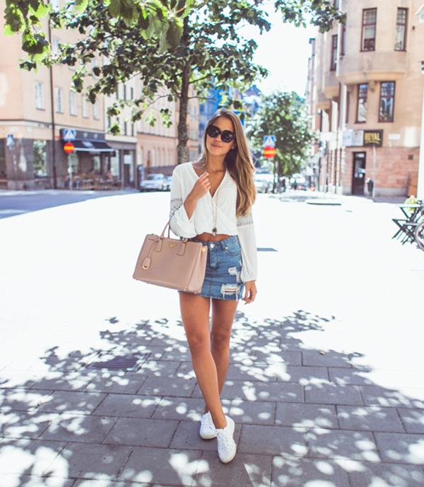 Distressed and frayed denim skirts are always a winner! Kenza Zouiten pairs this cute vintage style skirt with a cropped white blouse and sneakers, creating an easy and stylish summer look. Skirt: Asos, Top: H&M, Shoes: Superga, Bag: Prada.