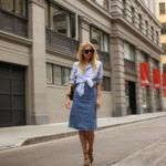 Blair Eadie is wearing a knot tied blue shirt and a long denim skirt outfit Skirt: Stella McCartney, Shoes: Zara. Top: Haute Hippe