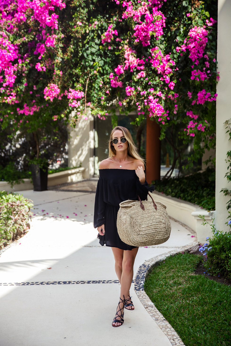 Kristin Sundberg is rocking the off-the-shoulder trend in a cute and casual black shoulderless dress, paired with a straw beach bag and strappy sandals. Everything about this look screams 'summer', and we love it! Brands not specified.