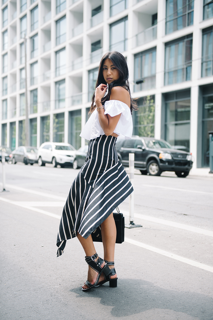 Why not try wearing an off the shoulder blouse like this one with a statement maxi skirt? Kayla Seah is rocking this look, pairing a simple white top with a vibrant asymmetrical skirt for an overall edgy and alternative look! Skirt: Third Form, Top: Zara, Sandals: Isabel Marant, Bag: Gucci.