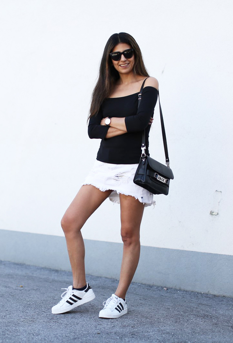 The simplest of outfits: Black off-the-shoulder top paired with a white denim skirt and black and white sneakers. Via Laura Dittrich Skirt: One Teaspoon, Top: Asos, Sneakers: Adidas Superstar II, Sunglasses: Céline, Bag: Proenza Schouler