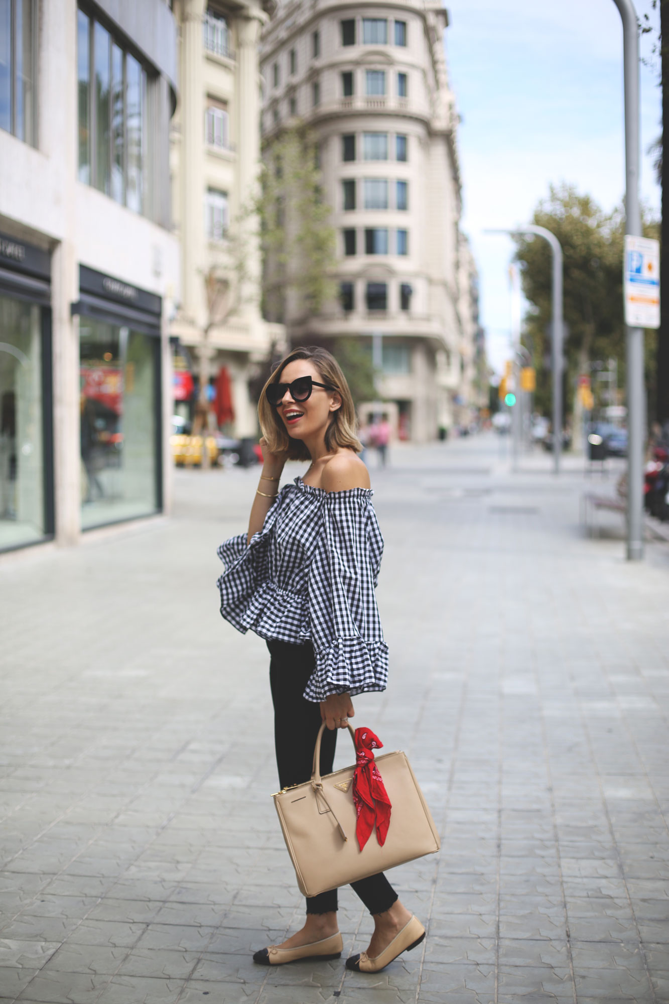 An off the shoulder cut can really accentuate your shape, and looks especially cute when worn on a statement print top such as this gingham blouse worn by Priscila Betancort. We love this cute and summery look! Top: Chicwish, Jeans: Zara, Shoes: Chanel, Bag: Prada.