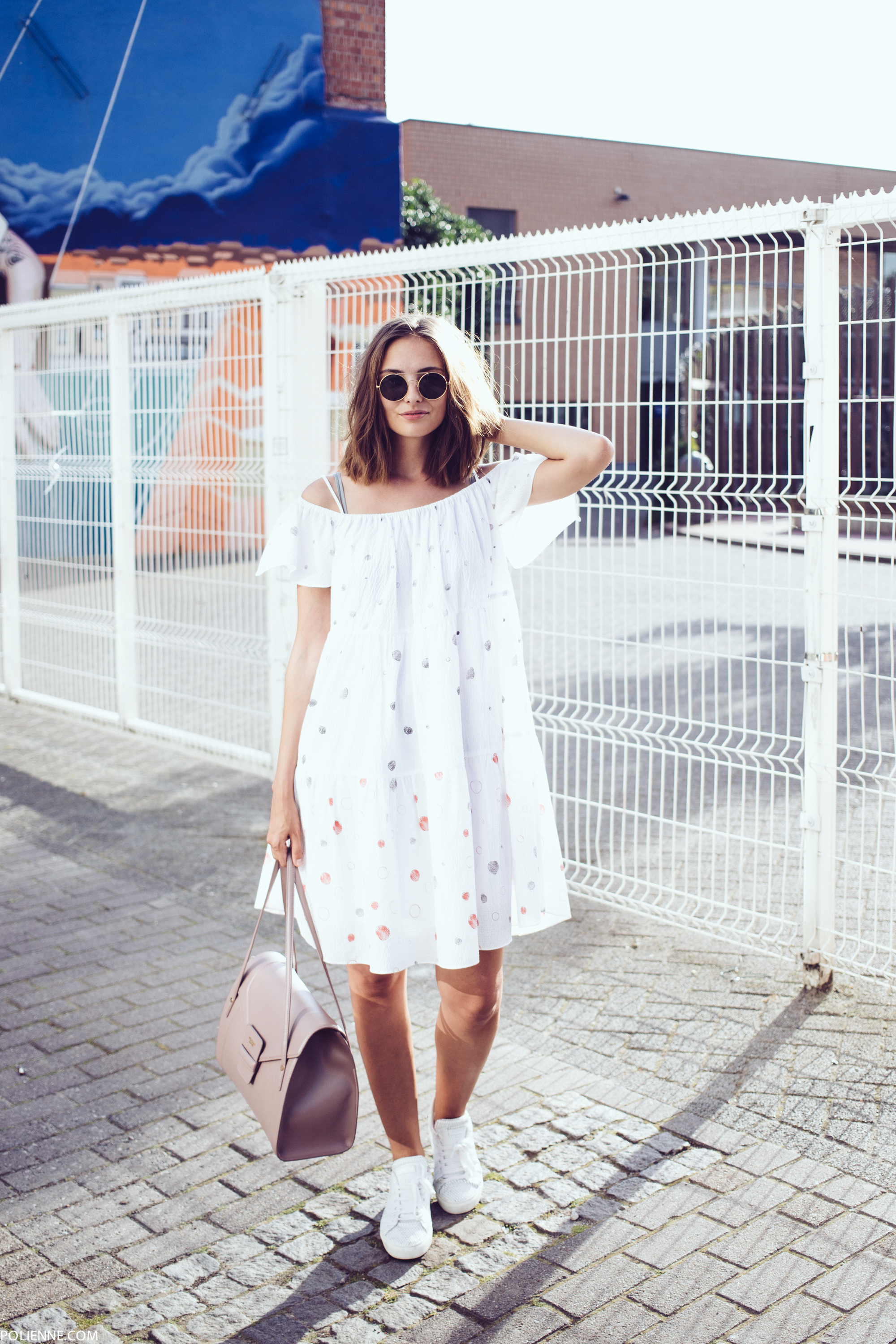 A loose fitting white dress such as this one worn by Rosanna van Billie-Rose is this year's must have off the shoulder piece! Paired with sneakers and a stylish blush pink leather bag, this dress looks cute and elegant. Dress: & Other Stories, Sneakers: Pinko.