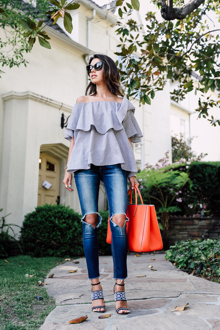 A floaty and layered off the shoulder top will give you a gorgeous feminine look which is perfect for every day spring and summer wear. Match this style with patterned sandals to get Annabelle Fleur's style. Top: Mlm Label Maison, Jeans: Blank Denim, Sandals: Tabitha Simmons.