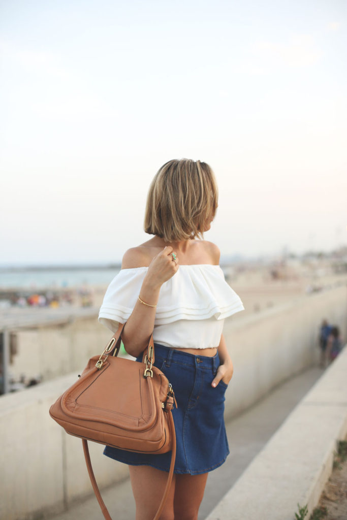 Pair your off the shoulder top wit a short denim skirt. It couldn't be more on trend at the moment. Via Priscila Betancort  Top: Oxygene, Skirt:Zara, Bag . Chloé.