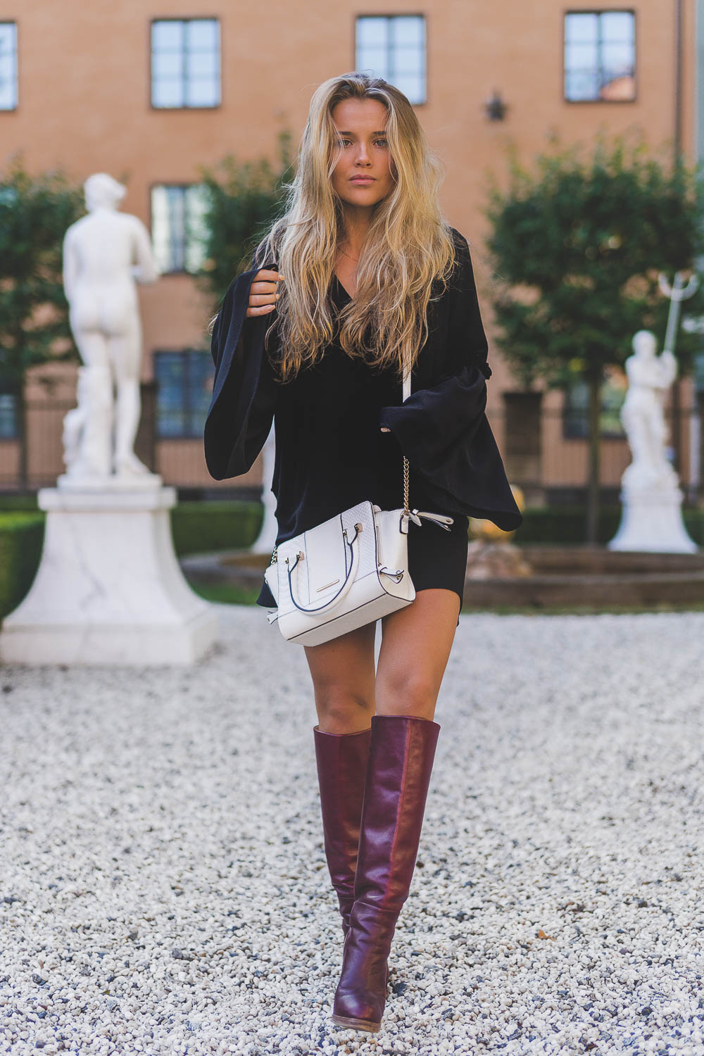 Molly Rustas wears a simple but sophisticated bell-sleeved black tunic with a cute pair of over the knee boots. Dress: Patrick Guetta.