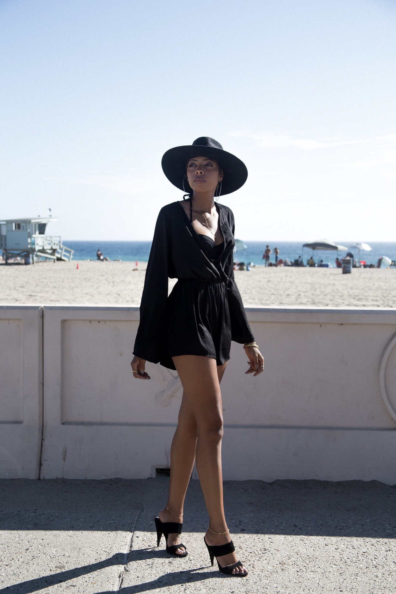 Try wearing a bell sleeved black playsuit with a stylish hat and heels. Via Bambisarmoire.com. Playsuit: Brandy & Melville, Heels: Steven Madden.