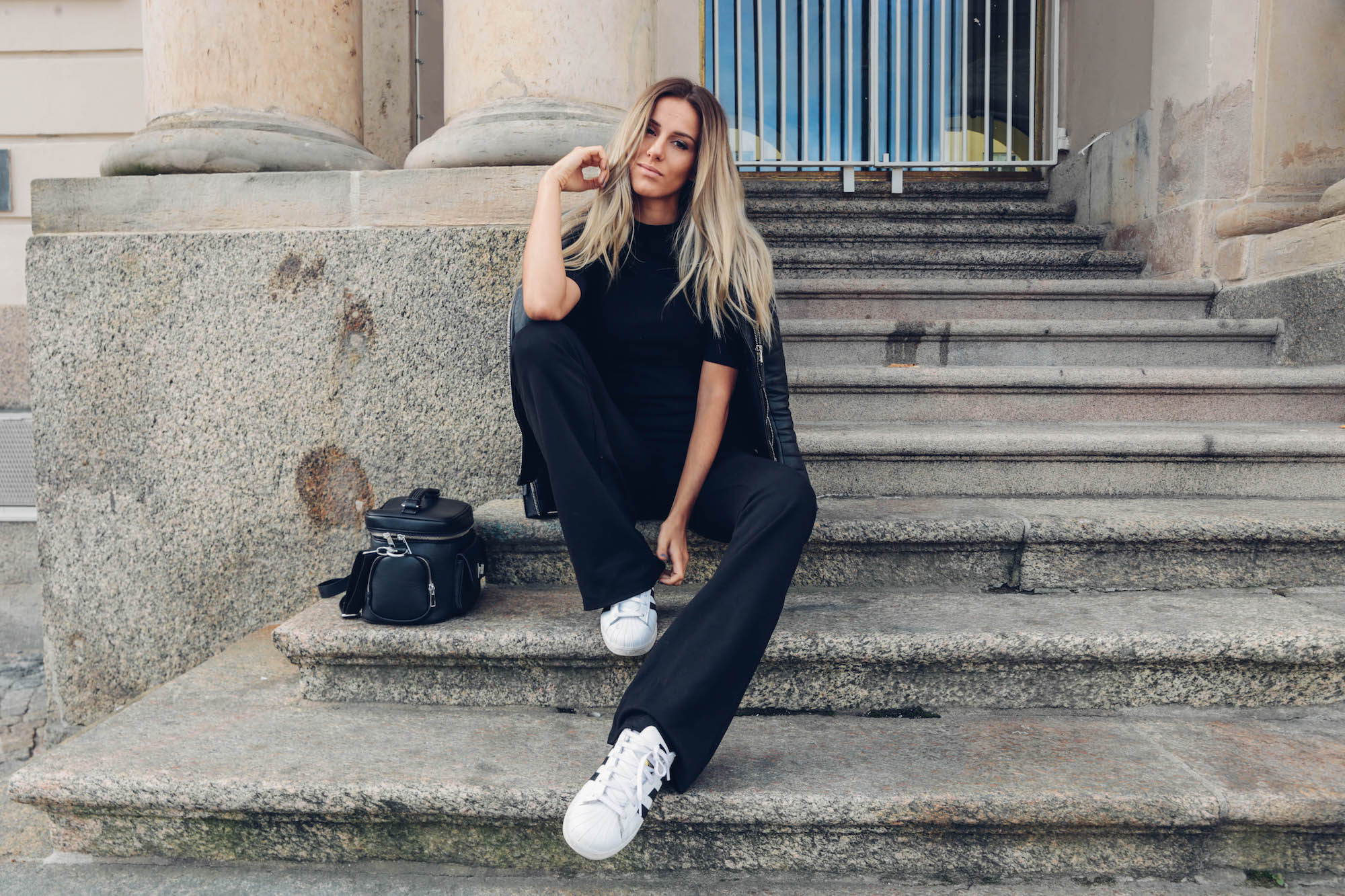 Break up your black on black outfit with some pristine white sneakers. Via Skopljak. Top/Trousers: Gina Tricot, Shoes: Adidas, Bag: Rut & Circle.