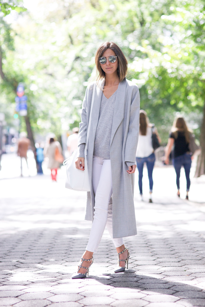 Arielle Nachami wears sophisticated grey coat with tight white trousers and statement heels. Jeans/Coat: AYR, Sweater: Everlane, Shoes: Valentino.
