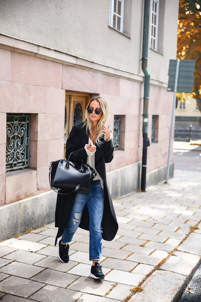 This black maxi coat is simple but effective when paired with distressed denim jeans and black sneakers. Via Chiara Ferragni.  Coat: Ikrush, Knit: Kappahl, Sneakers: Puma.