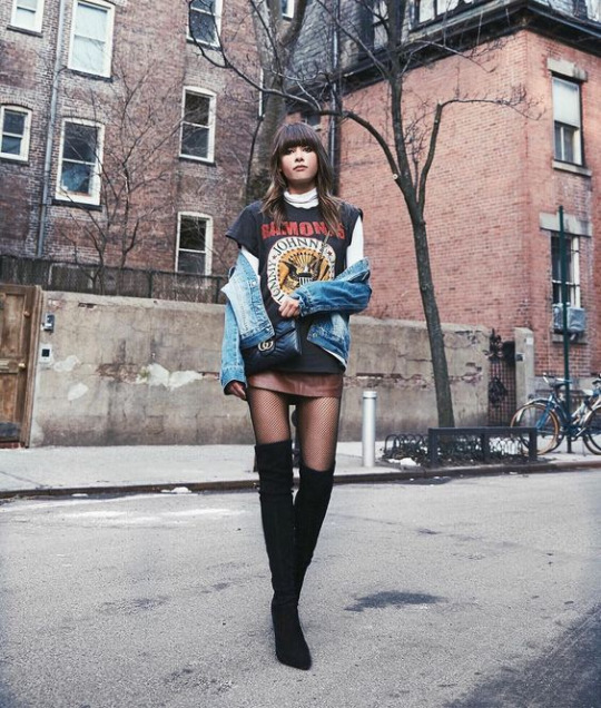 Michelle is wearing striking over the knee boots with tights and a mini skirt, creating an edgy street style we love. She pairs these with a layered band tee and denim jacket, exuding 70s vibes all round.   Skirt: DKNY, Boots: Sam Edelman, Shirt: Suncoo Paris.