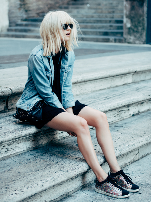 The black canvas with the denim jacket and sequin sneakers makes this an easy rocker style to copy. Also love the studded bag. Via Rima Vaidila  Dress: Wilfred, Myosotis, Denim Jacket: AG Jeans, Bag: Saint Laurent, Sneakers: Isabel Marant