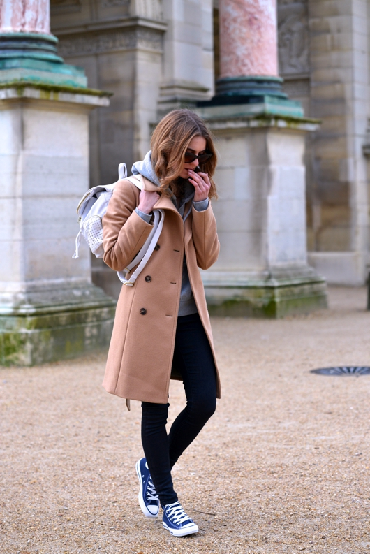 A camel coloured coat and black skinny jeans go wonderfully with a pair of navy converse. Via Katarzyna Tusk.   Trousers: Moto by Topshop, Hoodie: Abercrombie & Fitch, Coat: Sisley, Shoes: Converse.