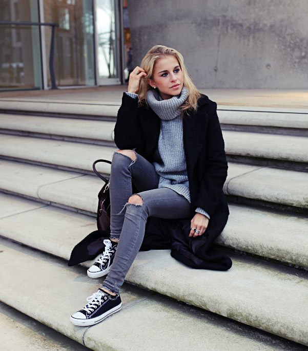 Caroline Daur is a vision in greyscale, wearing a pair of simple black and white converse with ripped grey jeans and a matching turtleeck to create an easy but sophisticated style. Sweater/Jeans: Review, Shoes: Converse, Bags: Aigner, Coat: Asos.