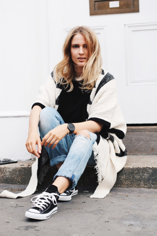 Converse are the perfect footwear choice for an outfit such as Mirjam Flatau's, which consists of a destroyed black tee, oversized distressed denim, and an aztec style poncho. Poncho: Edited, Jeans/Tee: Citezens Of Humanity, Shoes: Converse.