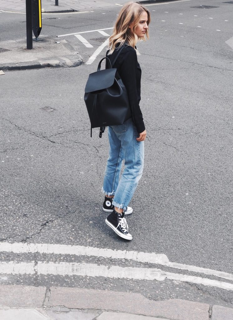 Ankle high converse look edgy and sleek when worn with ripped mom jeans and a casual black shirt. Via Mirjam Flatau.  Jeans: Levi, Shoes: Converse, Shirt: Rails