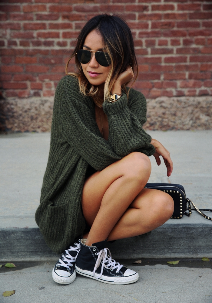 Julie Sarinana wears a cute green knit cardigan with her ankle high chuck taylors. Classic black converse really do go with anything! Cardigan: Anine Bing, Converse.