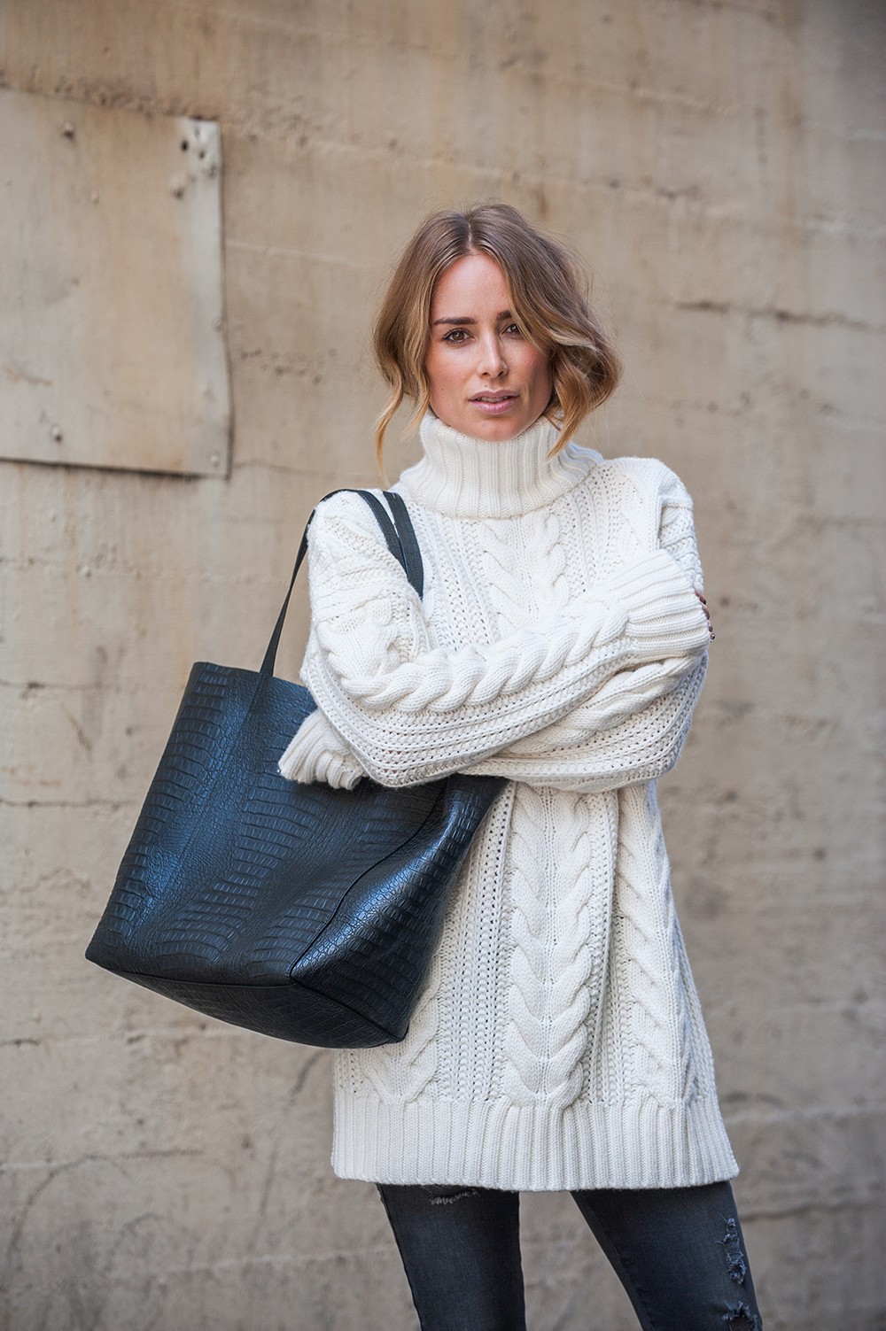 Anine Bing wears a gorgeous cream turtle neck knit over distressed skinny jeans, accessorising with a black faux snakeskin bag. Outfit: Anine Bing.