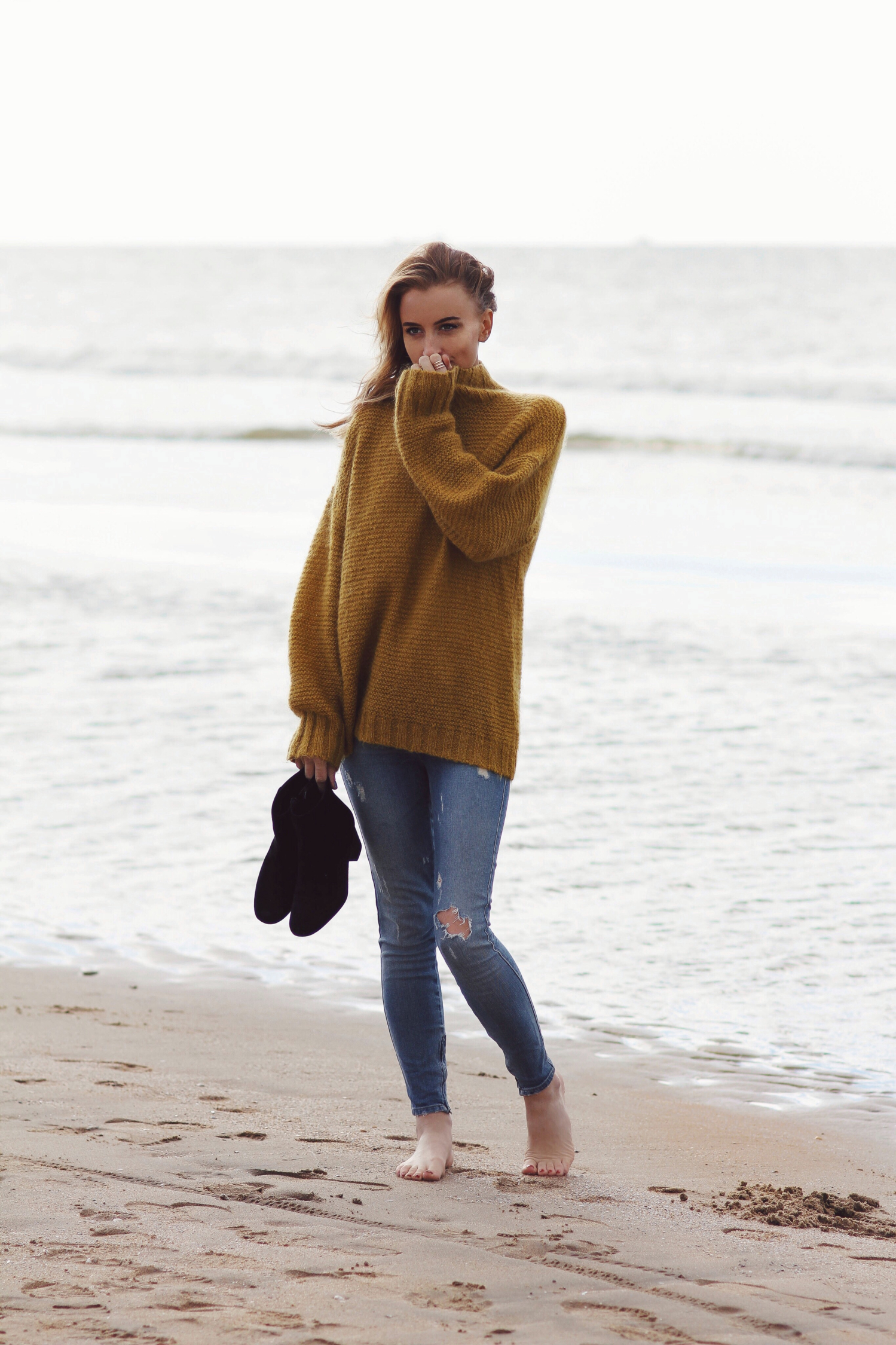 Noor De Groot wears a cute mustard knit and ripped denim jeans. Sweater: Baum und Pferdgarten, Jeans: Ksubi, Booties: Sam Edelman.